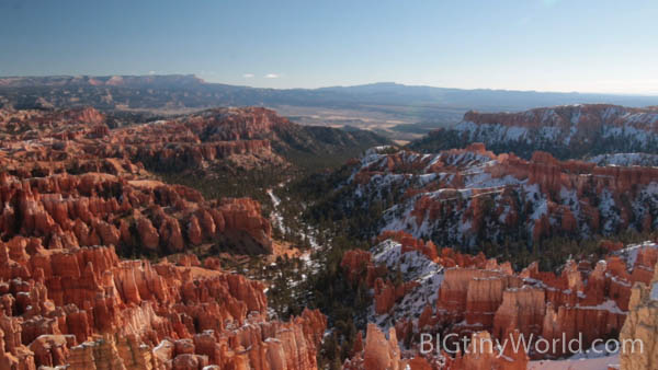 A landscape of hoodoos with a dividing line of trees separating the snow covered from the bare | bigtinyworld.com