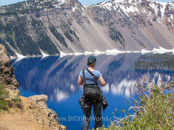 Brianna standing in front of the brilliant blue Crater Lake | BIGtinyWorld Travel