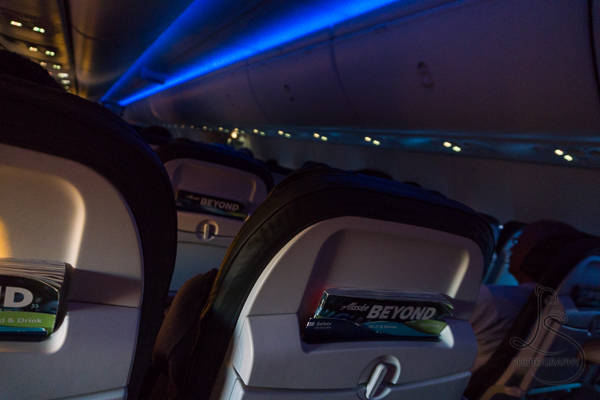 The darkened cabin for our international flight | BIG tiny World Travel