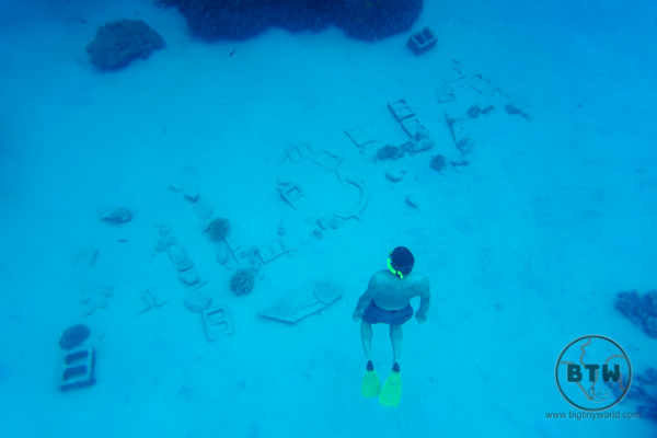 A diver admiring the word Aloha at the bottom of a snorkel spot in Hawaii